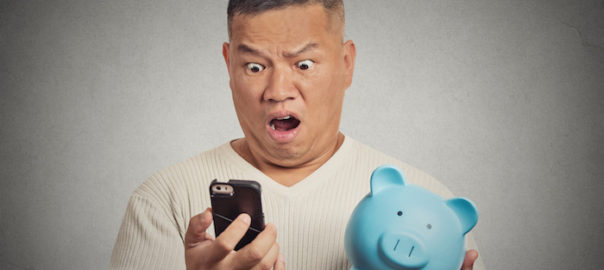 Portrait shocked man looking at his smart phone holding piggy bank